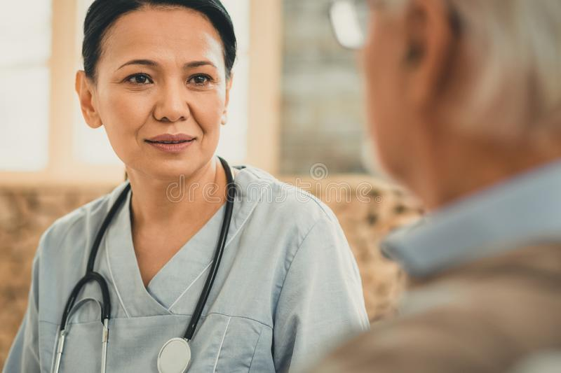 Pleasant calm nurse with stethoscope working with patient. Severe conversation. Pleasant calm nurse with stethoscope working with patient wearing blue special stock photography