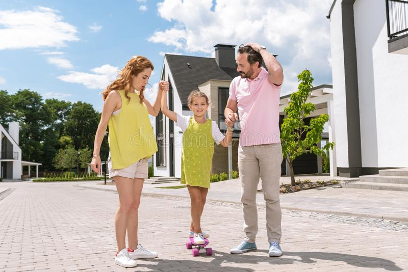 Pleasant caring parents holding their daughters hands. Be careful. Pleasant caring parents holding their daughters hands while helping her to skate royalty free stock photo