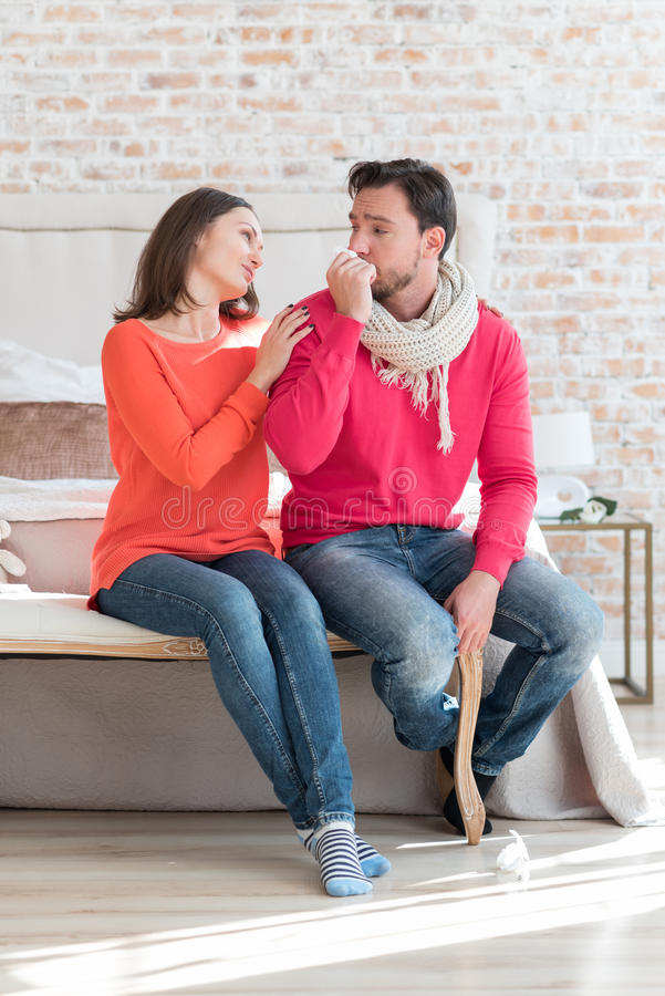 Pleasant caring wife supporting her ill husband royalty free stock images