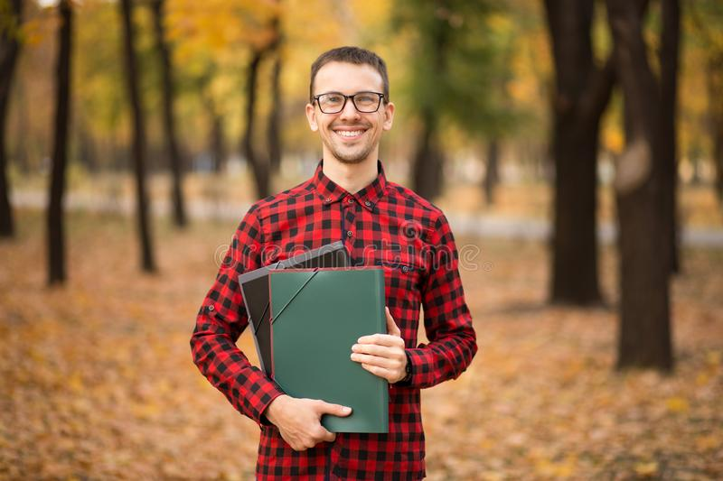 Pleasant cheerful handsome realtor holding folder and expressing positivity while standing in autumn park stock photography