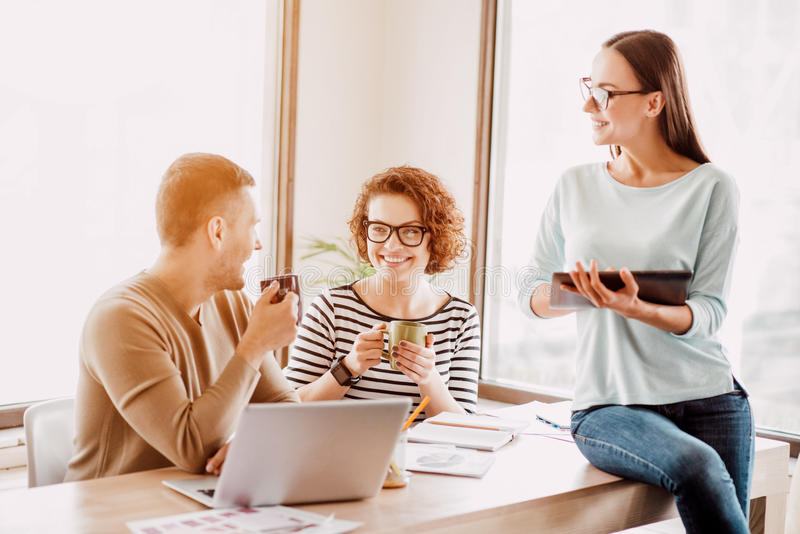 Pleasant colleagues sitting in the office. Have a break. Pleasant cheerful delighted colleagues sitting at the table and drinking coffee while resting in the royalty free stock photos