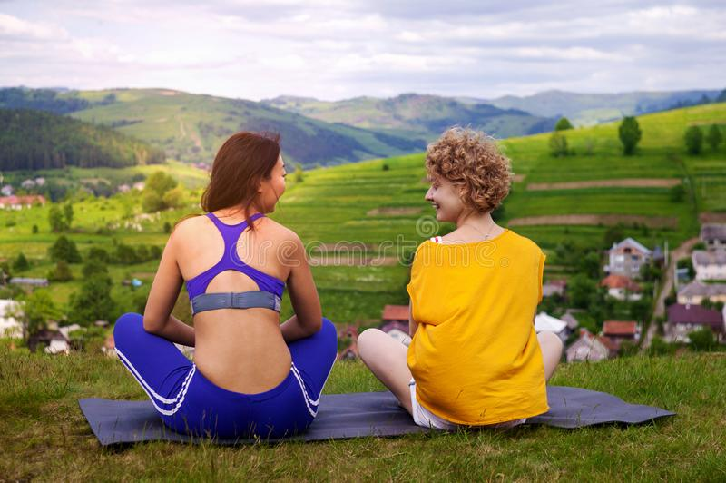 Pleasant communication. Happy delighted young woman smiling and talking to her friend while sitting on  yoga mat. royalty free stock image