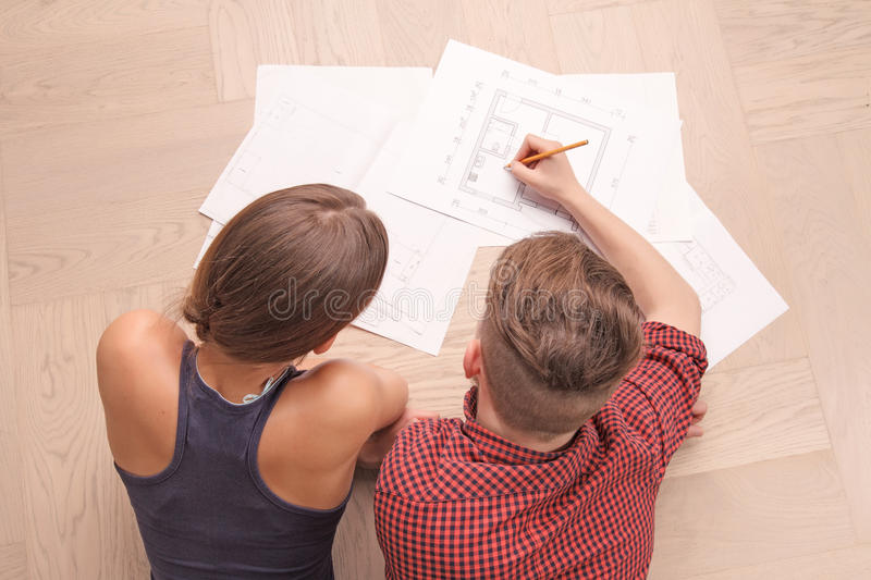 Pleasant couple drawing plan stock photography