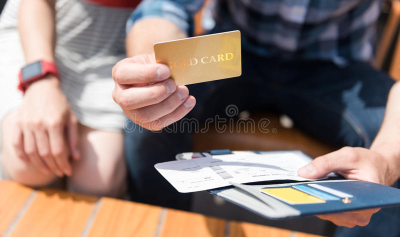 Pleasant couple sitting on the bench. VIP clients. Pleasant men holding his purse and getting credit card while sitting on the bench with his girlfriend stock photos
