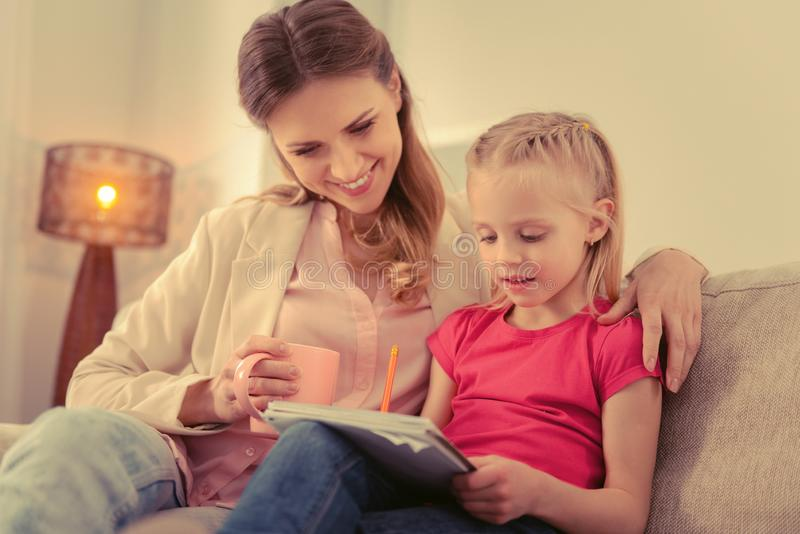 Pleasant cute girl doing her homework with her mother stock image