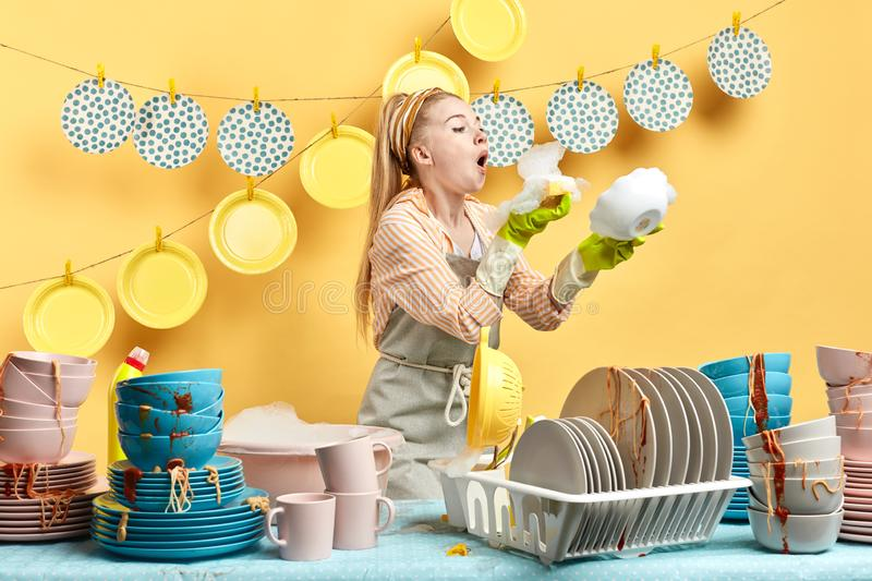 Pleasant cute woman in gray apron having fun with foam royalty free stock images