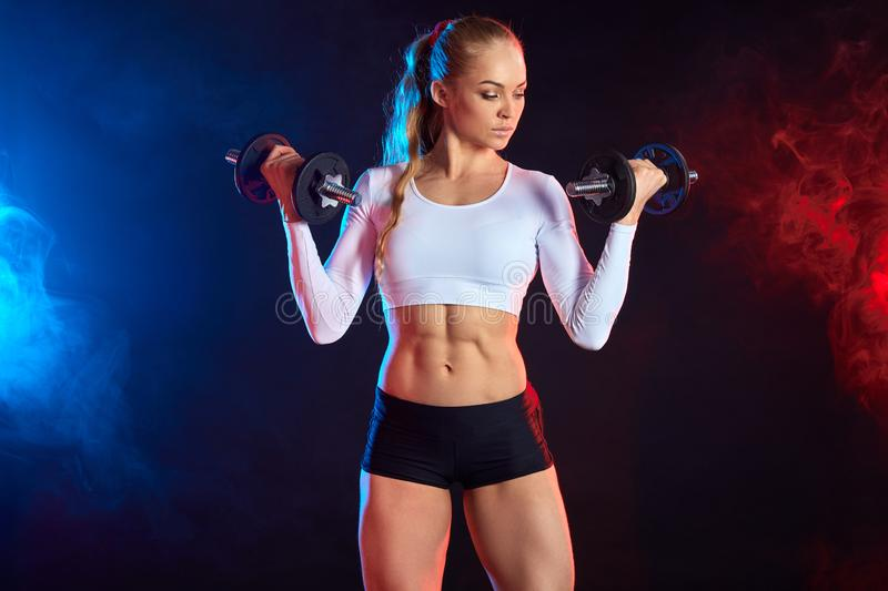 Pleasant cute woman leraning to train with dumbbells stock image