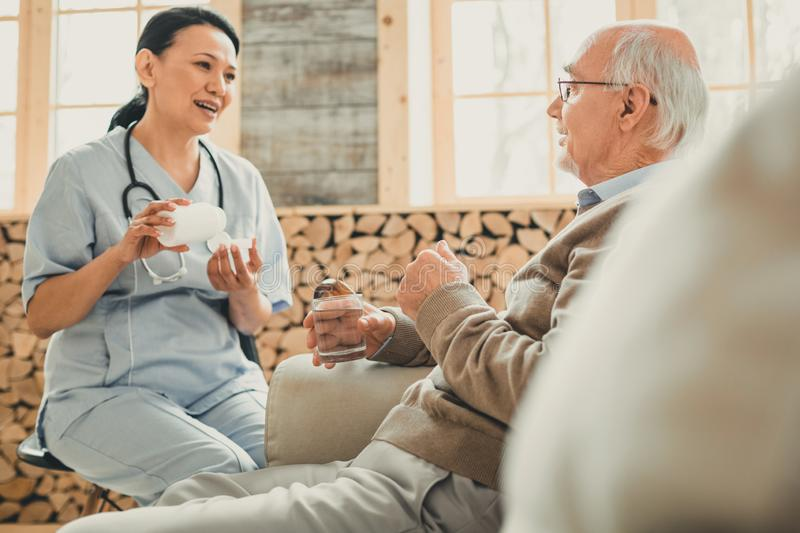 Pleasant dark-haired woman in blue confidently talking to patient. Smiling kind woman. Pleasant dark-haired women in blue confidently talking to partly-bald old royalty free stock photo
