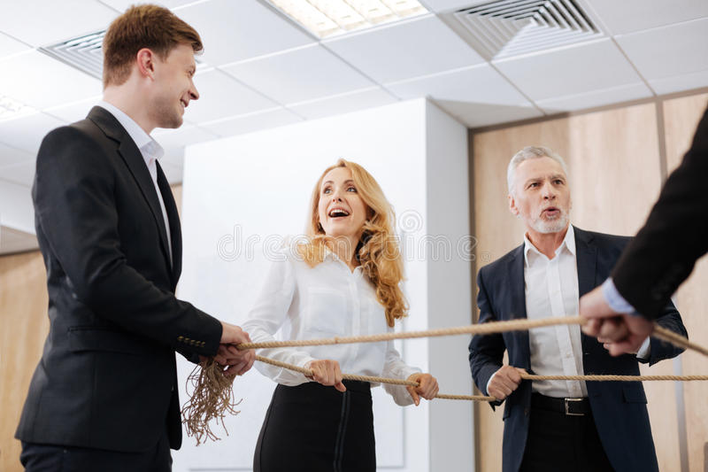 Pleasant delighted colleagues looking at each other. Team building exercise. Pleasant delighted nice colleagues holding a rope and looking at each other while stock image