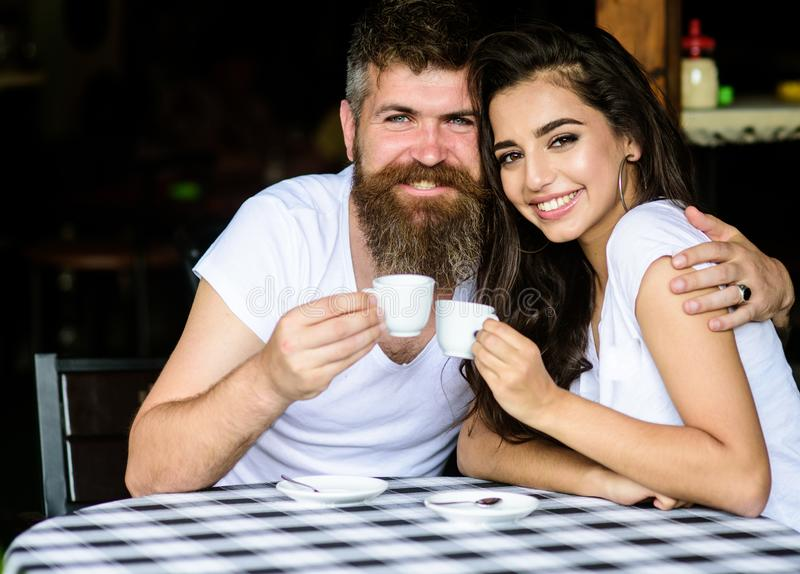 Pleasant family moment. Couple in love drink black espresso coffee in cafe. Man with beard and attractive happy smiling royalty free stock images
