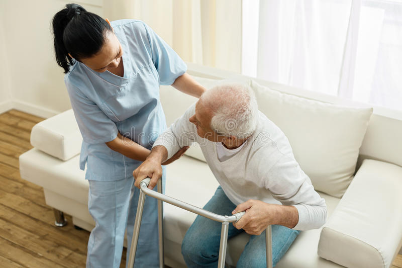 Pleasant friendly caregiver doing her job royalty free stock photography