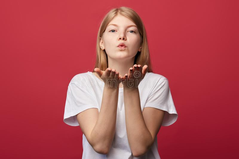 Pleasant friendly woman in white T-shirt sending a kiss royalty free stock image