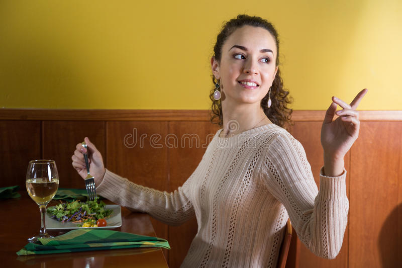 Pleasant girl calls up the waiter in a restaurant royalty free stock image