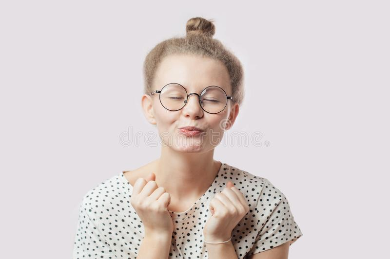 Pleasant girl with hairbun and glasses blowing sweet kiss. stock image