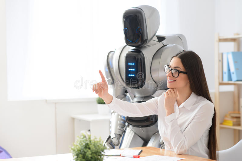 Pleasant girl sitting in the office with robot royalty free stock photos