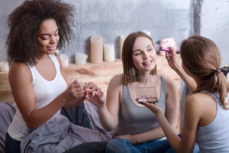 Pleasant girls helping her friend getting ready at home. My helpful friends. Pleasant delighted young girls sitting on the bed and helping her friend to get royalty free stock photos