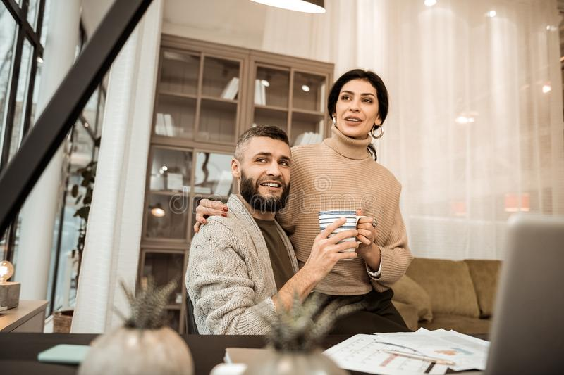 Pleasant good-looking couple spending time together in cabinet royalty free stock photo