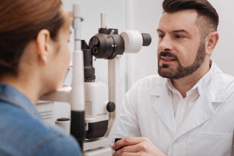 Pleasant good looking oculist using eye testing equipment royalty free stock images