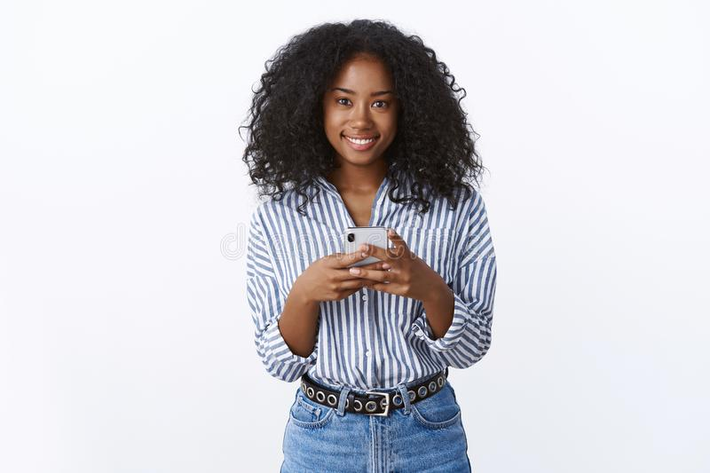 Pleasant gorgeous friendly-looking african american girlfriend wearing modern stylish blouse holding smartphone smiling. Broadly nice outgoing attitude, edit royalty free stock images
