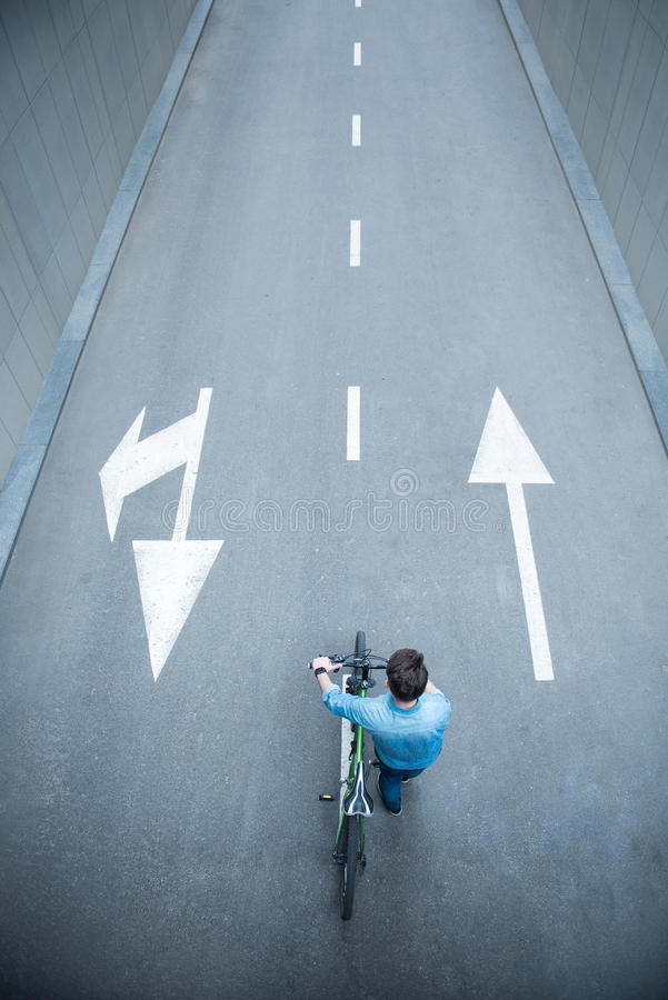 Pleasant guy walking along the road with bicycle royalty free stock photography