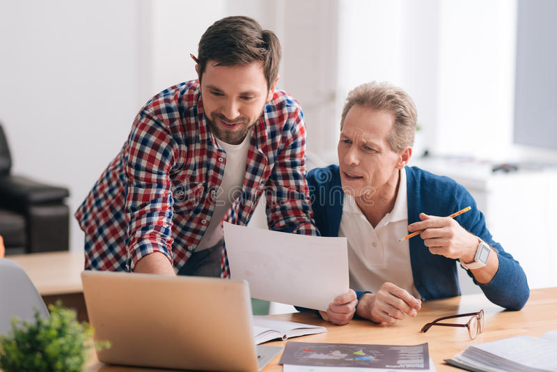 Pleasant handsome man showing something to his colleague. Cooperation and partnership. Pleasant handsome nice men leaning forward and showing something on the royalty free stock photo
