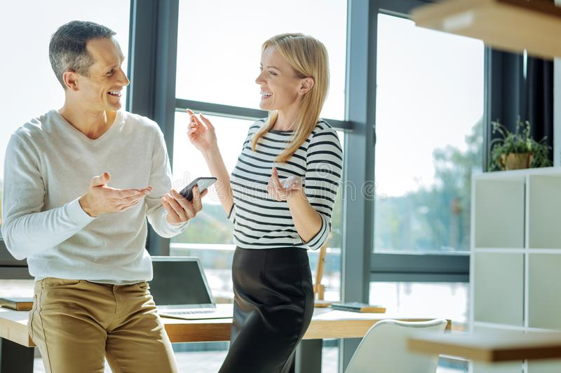Delighted positive colleagues talking to each other. Pleasant interaction. Delighted positive nice colleagues standing against the window and laughing while stock image