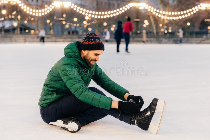 Pleasant looking man wears green coat and hat, sits on ice and l. Aces up skates, going to skate, has happy expression. Handsome man spends winter holidays on royalty free stock images