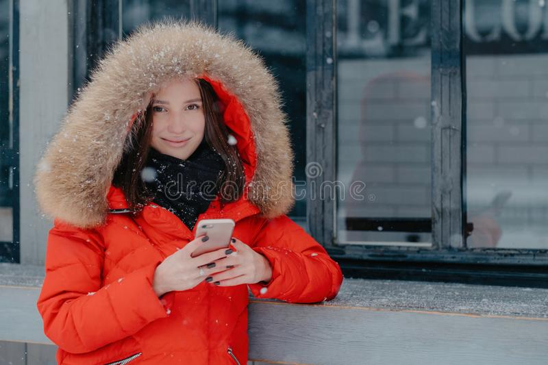 Pleasant looking young female in red jacket, holds modern smart phone, checks bank account, waits for call, enjoys online royalty free stock photography