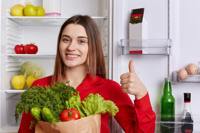 Pleasant looking of young woman with long straight hair, dressed in red blouse, holds paper bag with vegetables, shows ok sign, st stock photo