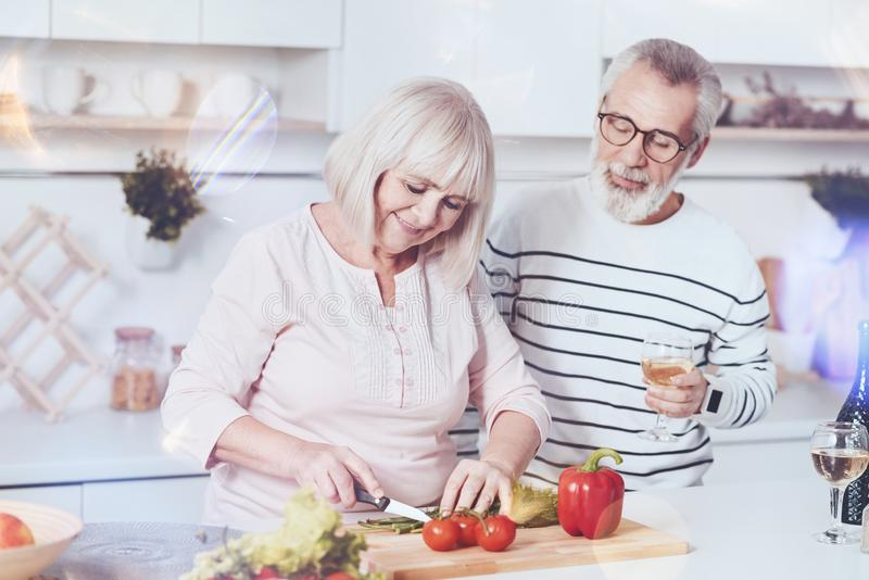 Pleasant loving aged couple making vegetable salad royalty free stock photos