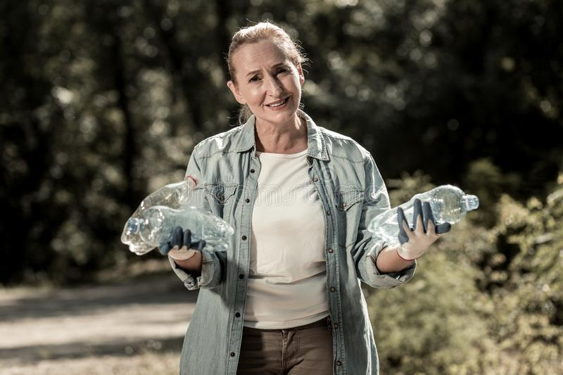 Pleasant mature blonde-haired woman begging people not leaving garbage outside. Begging people. Pleasant mature blonde-haired woman wearing bright gloves begging stock photos