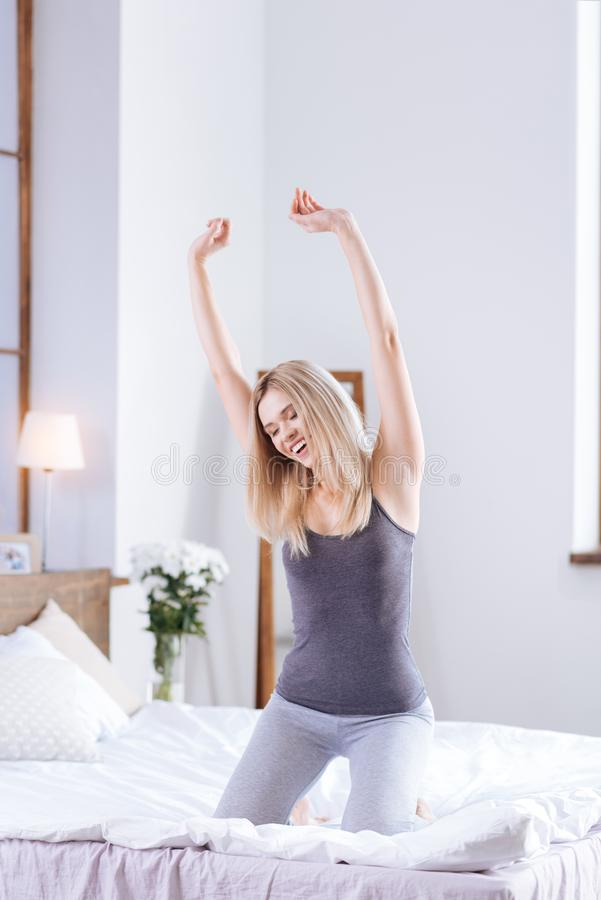 Cheerful woman stretching herself while sitting on the bed stock images