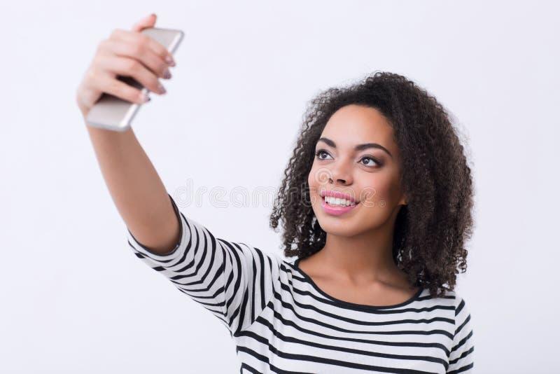 Pleasant mulatto woman making selfies royalty free stock photos