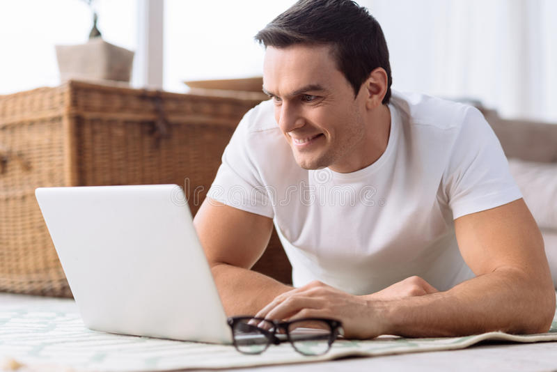 Pleasant nice man using touchpad stock image