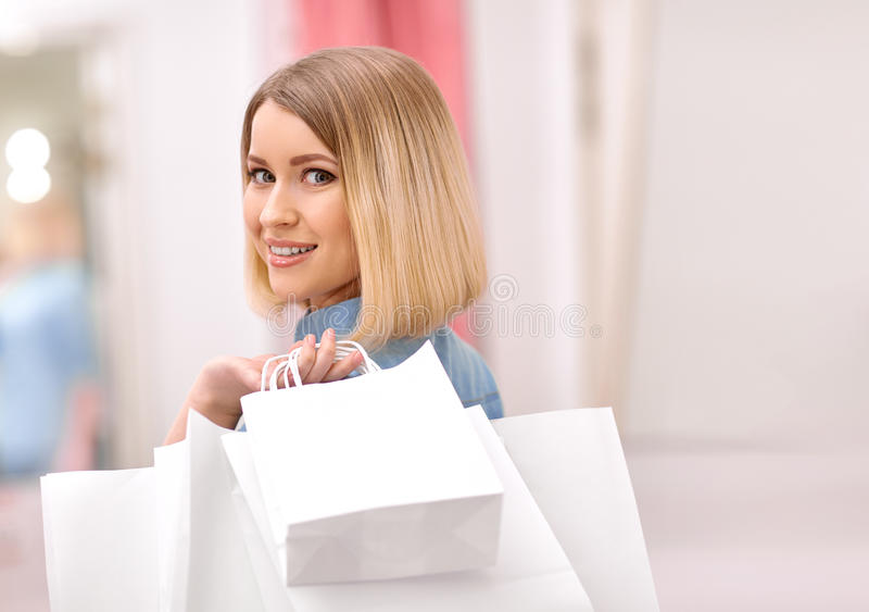 Pleasant positive girl shopping. Haunted paradise. Cheerful pleasant charming girl holding packages in hand and smiling while shopping royalty free stock photography