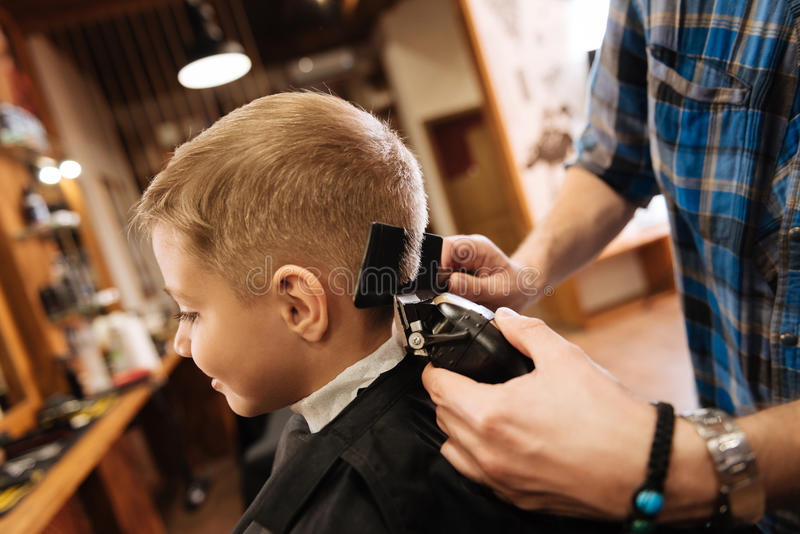 Pleasant professional barber using haircutting machine. New haircut. Pleasant professional nice barber holding a comb and using a hair cutting machine while royalty free stock images