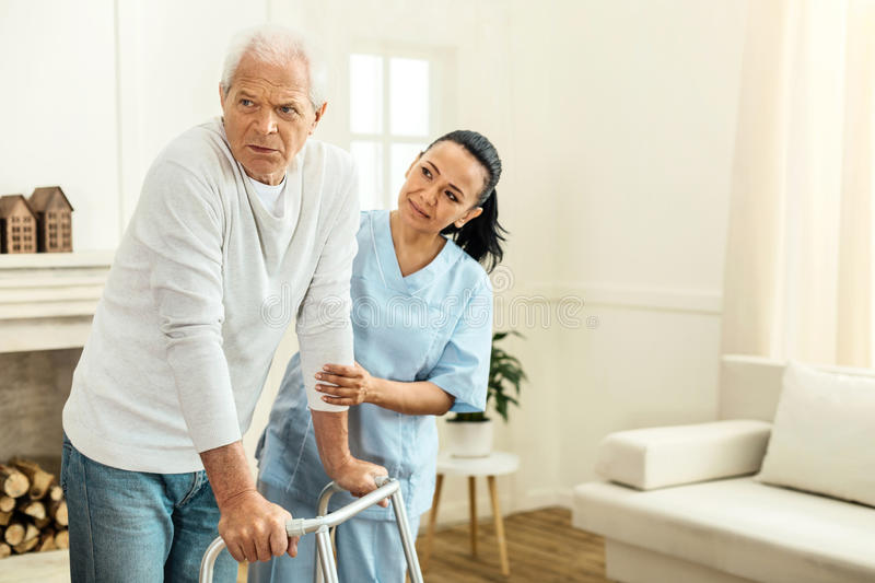 Pleasant professional caregiver holding her patients hand. Being supportive. Pleasant nice professional caregiver standing behind her aged patient and holding royalty free stock photos