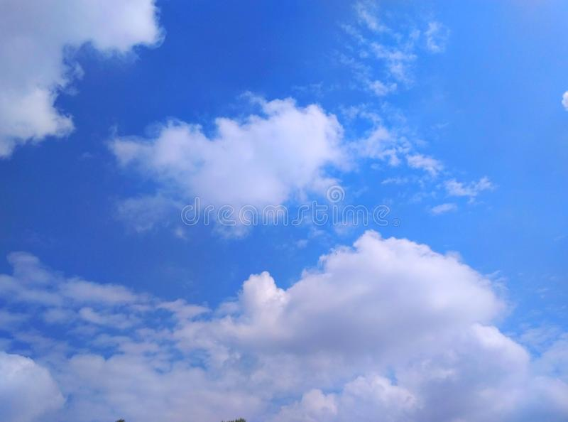 A pleasant rare view of shining white clouds in the blue sky royalty free stock photo