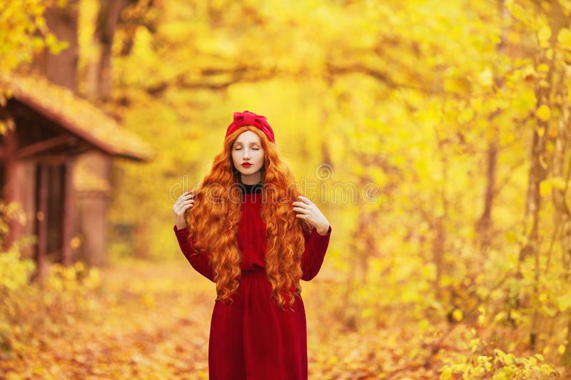 Pleasant redhead woman with long wave hair in red dress on autumn background. Pleasant october landscape. royalty free stock photo