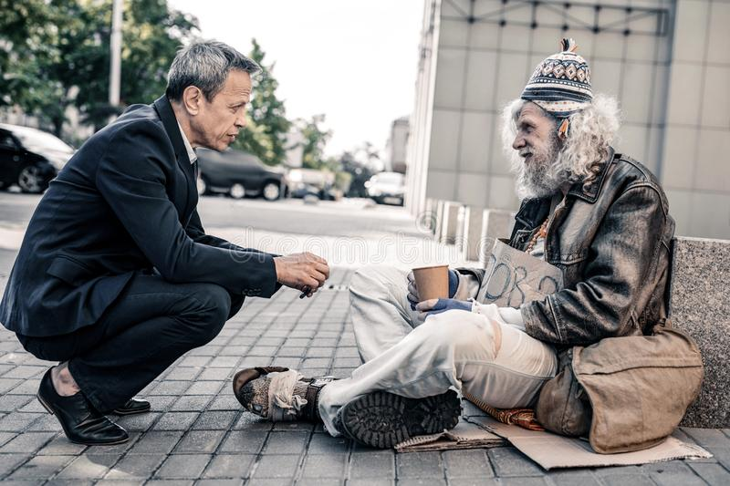 Pleasant short-haired rich man in costume supporting miserable homeless. Sincere conversation. Pleasant short-haired rich men in costume supporting miserable stock photos
