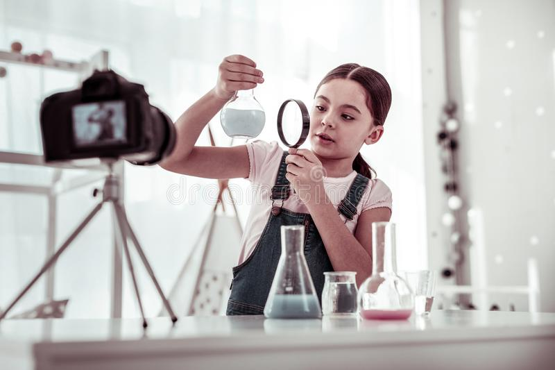 Pleasant smart young girl holding magnifying glass royalty free stock images