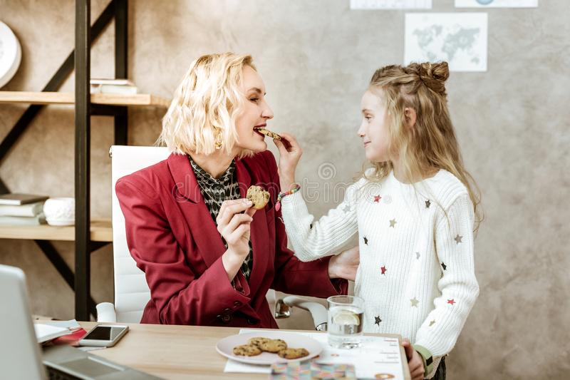Pleasant smiling light-haired little girl feeding her giggling mother royalty free stock images