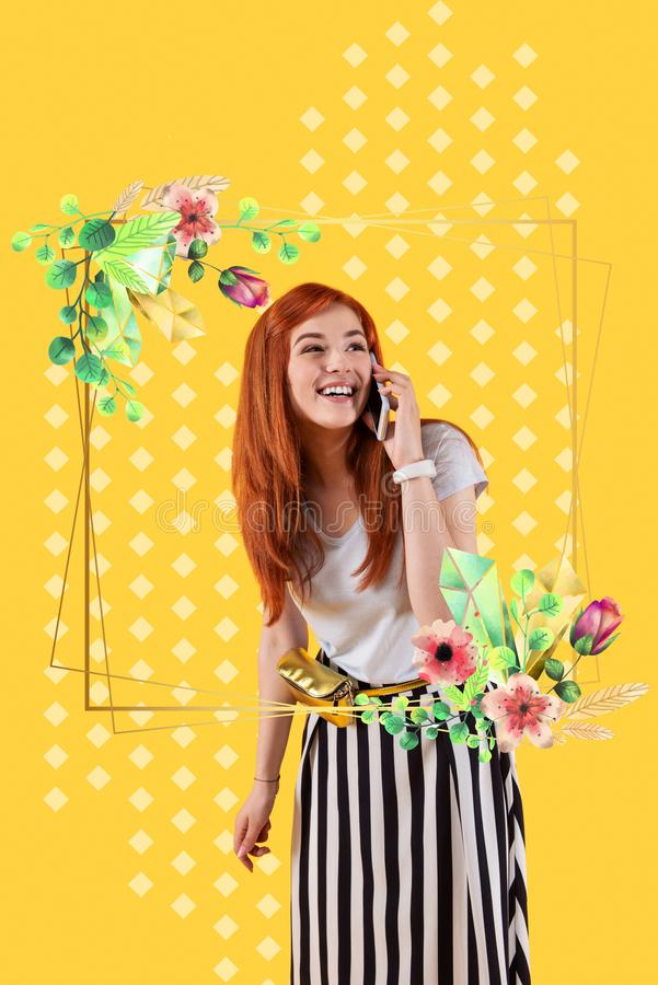Emotional girl looking out of the flowers and talking on the phone. Pleasant talk. Beautiful emotional girl smiling and feeling glad while looking out of the stock photos