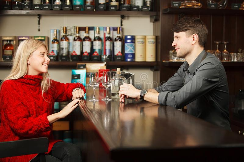 Pleasant talk between woman in bright red sweater and sommelier. Pleasant talk between women in bright red sweater and sommelier at bar counter, tasting royalty free stock photos