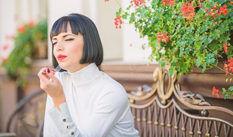 Pleasant time and relaxation. Delicious gourmet cake. Woman makeup face dreamy brunette eat cake cafe terrace background. Gastronomical enjoyment. Gourmet royalty free stock photography