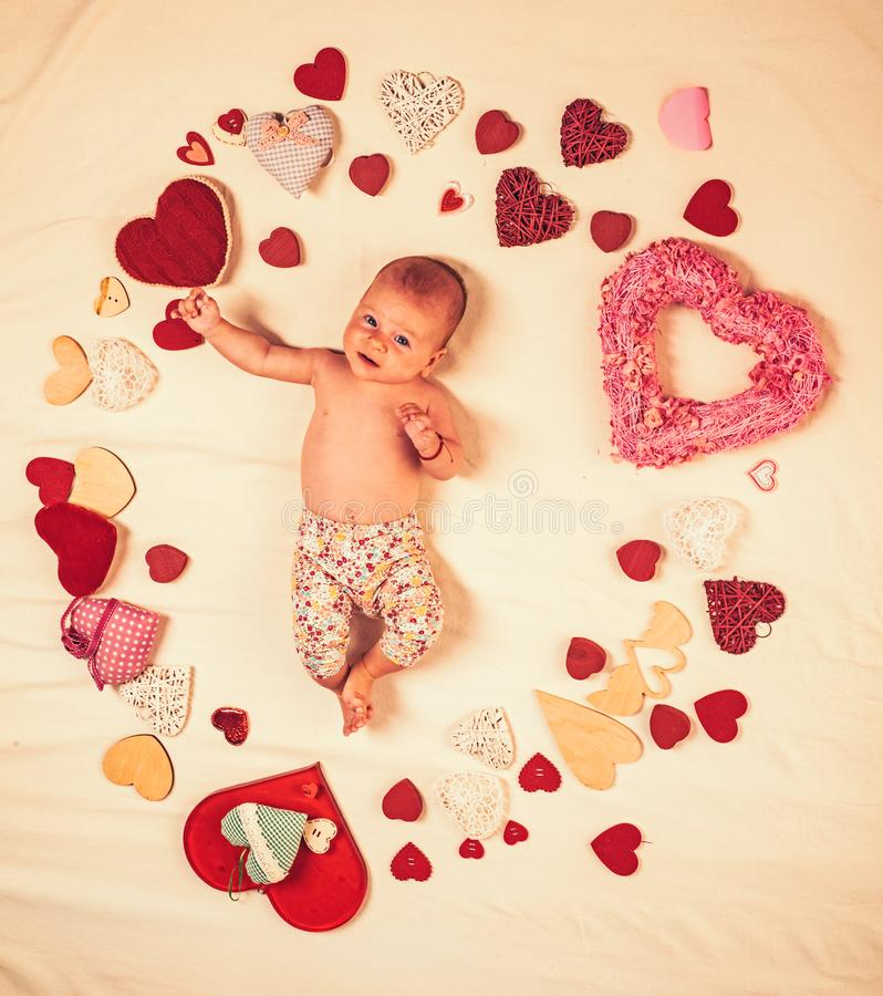 Pleasant timespending. Love. Portrait of happy little child. Sweet little baby. New life and birth. Family. Child care. Small girl among red hearts. Childhood stock photos