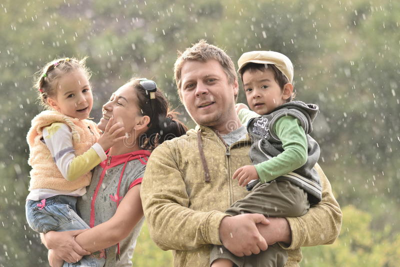 Happy family and cute kids on there hands in natur. Foto outdoor on a rainy day stock images
