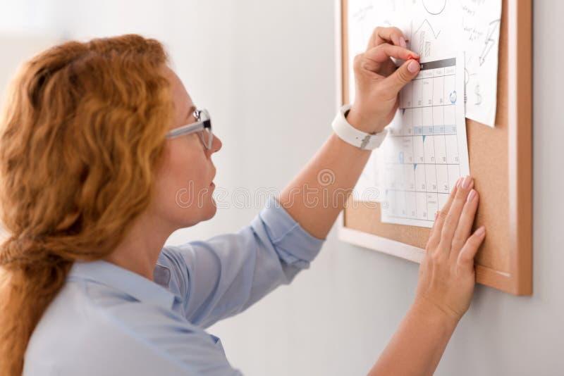 Pleasant woman holding the calendar stock photos