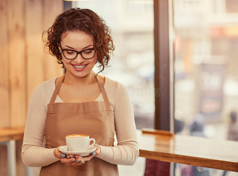 Pleasant woman holding cup of coffee. Unforgettable taste. Positive charming woman holding cup of coffee and expressing joy while standing in the cafe stock photo