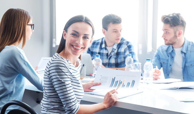 Pleasant woman holding diagrams stock images